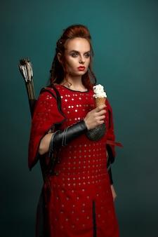 Schöne frau im mittelalterlichen kostüm, das eis hält.
