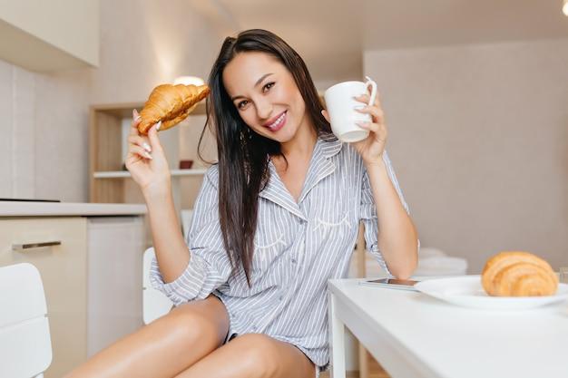 Schöne frau im niedlichen blauen pyjama, der mit lächeln während des frühstücks im gemütlichen raum aufwirft