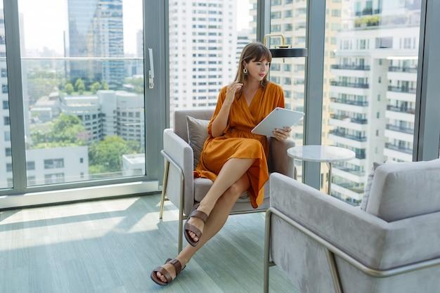 Schöne frau im orangefarbenen kleid mit tablette im modernen dachbüro.
