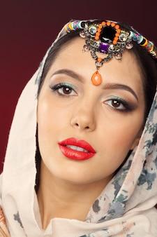 Schöne frau im orientalischen stil mit mehendi auf dunkel