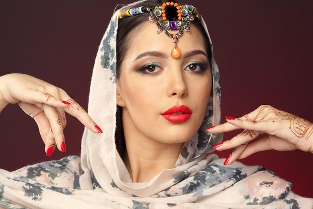Schöne frau im orientalischen stil mit mehendi auf dunklem hintergrund