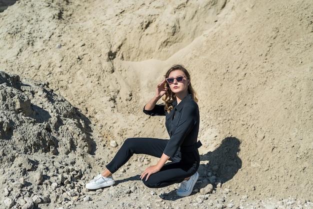 Schöne frau im overall, der für die kamera im sandsteinbruch, sommerzeit aufwirft