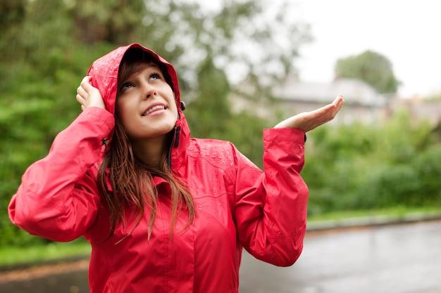 Schöne frau im regenmantel, die für regen prüft