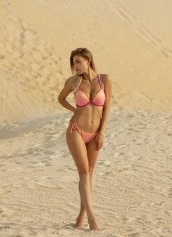 Schöne frau im rosa bikini, die sommersonne genießt und während der ferien am strand bräunt.