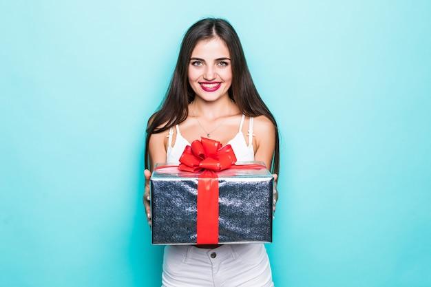 Schöne frau im rosa kleid, das auf einem großen geschenk sitzt und geschenkbox hält.