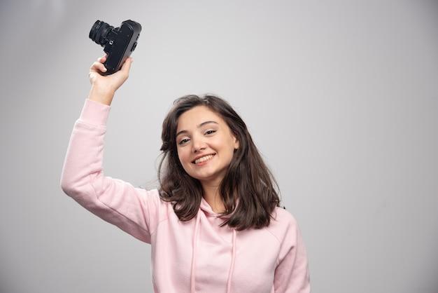 Schöne frau im rosa sweatshirt, das mit kamera aufwirft.