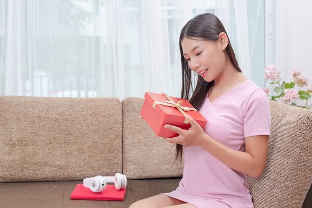 Schöne frau im rosafarbenen kleid, sitzend auf dem sofa und öffnen eine geschenkbox.