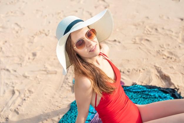 Schöne frau im roten badeanzug sitzt am strand