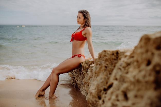 Schöne frau im roten bikini, der am strand auf felsen sitzend aufwirft