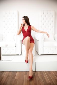 Schöne frau im roten catsuit und roten schuhen.