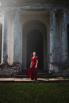 Schöne frau im roten kleid hintergrund altes herrenhaus