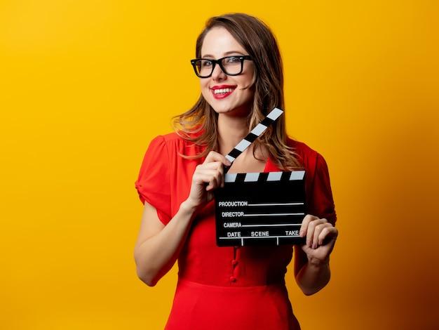 Schöne frau im roten kleid mit filmklappe