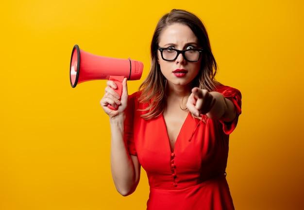 Schöne frau im roten kleid mit lautsprecher