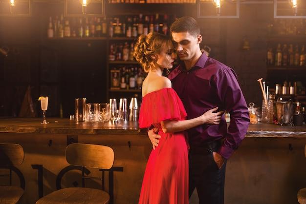 Schöne frau im roten kleid umarmt mit ihrem mann in der bar. date im nachtclub, attraktives liebespaar im pub