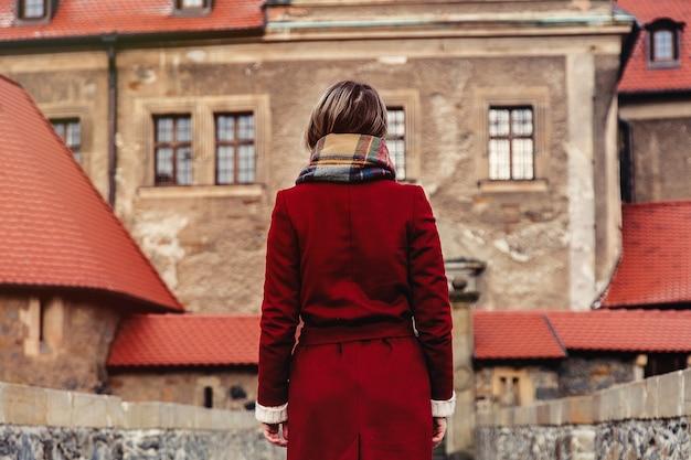 Schöne frau im roten mantel bleiben in der nähe von schloss