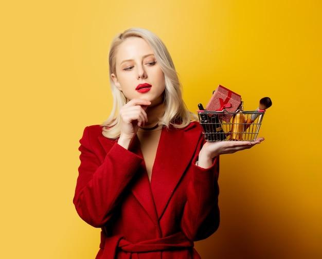 Schöne frau im roten mantel mit korb voller kosmetik auf gelber wand