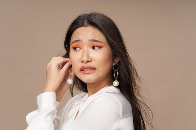 Schöne frau im runden ohrring-make-up auf gesicht und party