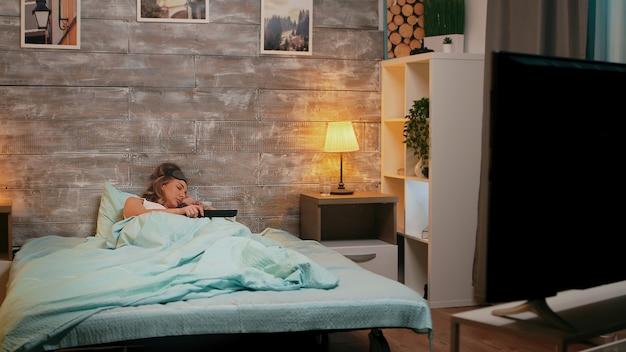 Schöne frau im schlafanzug, die schläft, während nachts der fernseher läuft. schlafmaske
