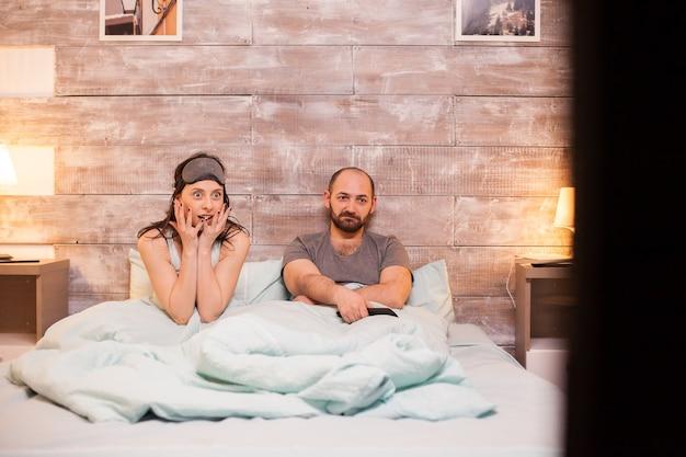 Schöne frau im schlafanzug, die zusammen mit ihrem gelangweilten ehemann einen schockierenden film im fernsehen sieht.
