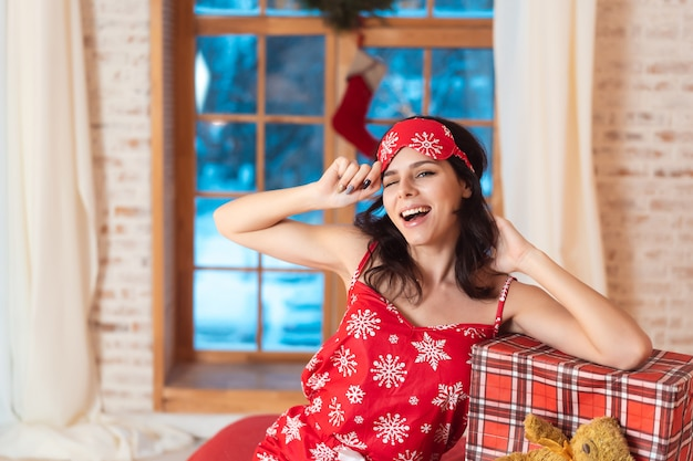 Schöne frau im schlafanzug mit geschenkbox