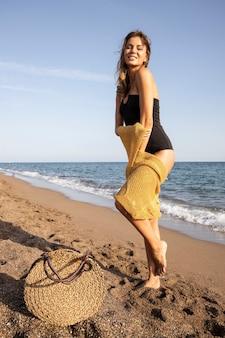 Schöne frau im schwarzen badeanzug am strand