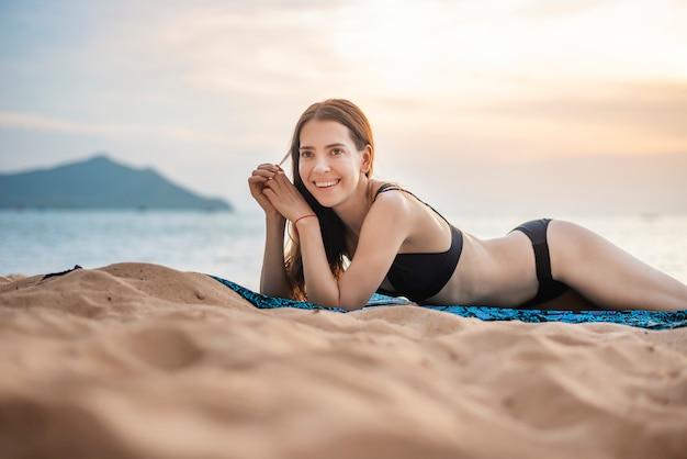 Schöne frau im schwarzen bikini liegt am strand