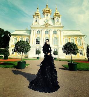 Schöne frau im schwarzen kleid, das neben dem palast aufwirft. dunkle königin.