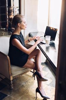 Schöne frau im schwarzen kurzen kleid arbeitet im stuhl mit laptop in der cafeteria. sie sieht beschäftigt aus.