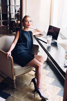 Schöne frau im schwarzen kurzen kleid sitzt im stuhl in der cafeteria. sie schaut zur kamera.