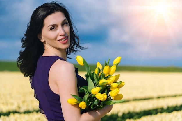Schöne frau im sommerkleid, die in bunten tulpenblumenfeldern steht