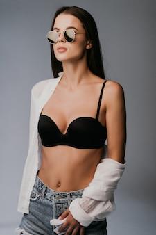 Schöne frau im sonnenbrillenkörper in den jeansjeanshorts lokalisiert in grau
