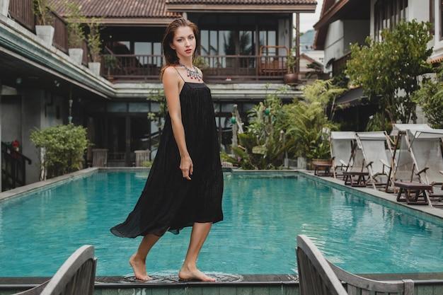 Schöne frau im stilvollen langen schwarzen kleid, das am pool der tropischen villa, eleganter sommerstil, urlaub, modetrend, barfuß gehen aufwirft
