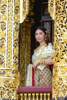 Schöne frau im thailändischen traditionellen outfit, das am tempel lächelt und steht