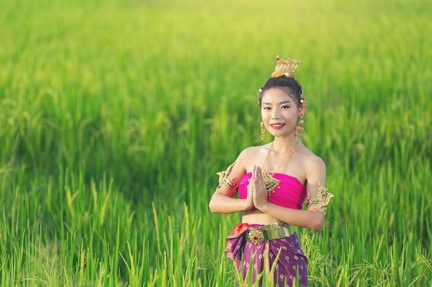 Schöne frau im thailändischen traditionellen outfit lächelnd und stehend am tempel