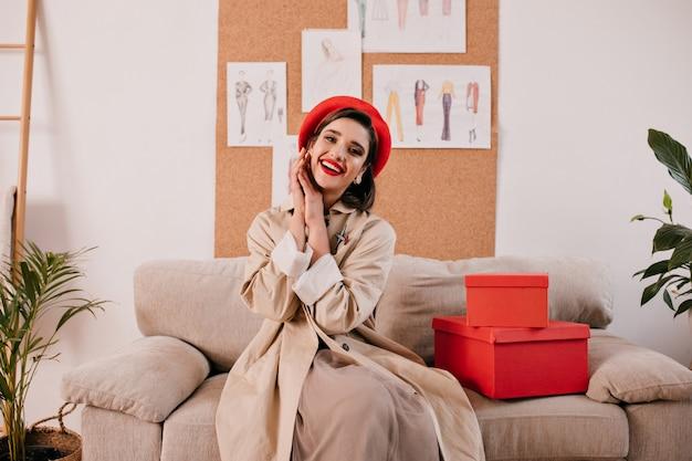 Schöne frau im trendigen graben und im französischen stil baskenmütze wirft in der wohnung auf. nettes mädchen in der roten baskenmütze und im herbst beige mantel lächelt.