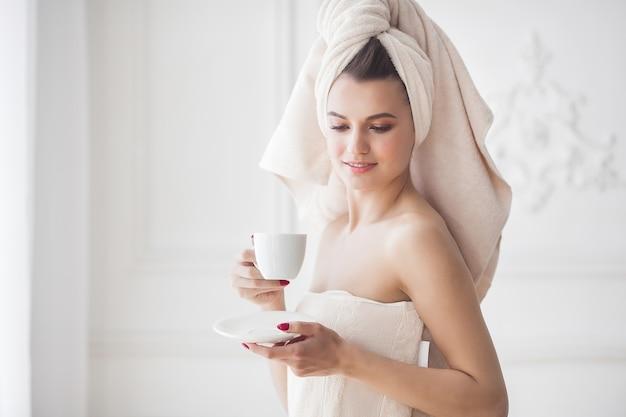Schöne frau im tuch, nachdem trinkender morgenkaffee gebadet worden ist