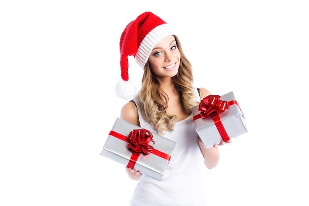 Schöne frau im weihnachtsmannhutlächeln, das eine stilvolle zwei kisten mit geschenken lokalisiert hält.