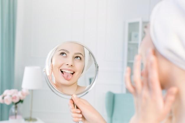 Schöne frau im weißen bademantel und im handtuch, die ihre perfekte haut im spiegel betrachten, zeigt die zunge und das auftragen von tonal cream base on face
