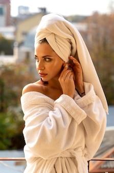 Schöne frau im weißen gewand und im handtuch auf dem balkon
