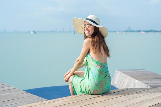 Schöne frau im weißen hut sitzt auf dem hotel mit dem strand