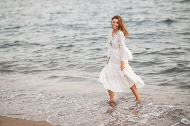 Schöne frau im weißen kleid am meer
