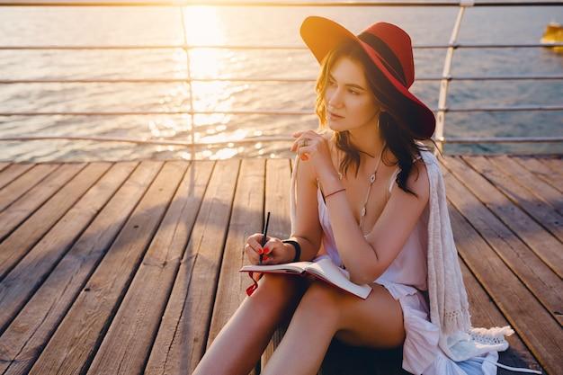Schöne frau im weißen kleid, das am meer auf sonnenaufgang denkt und notizen im tagebuchbuch macht
