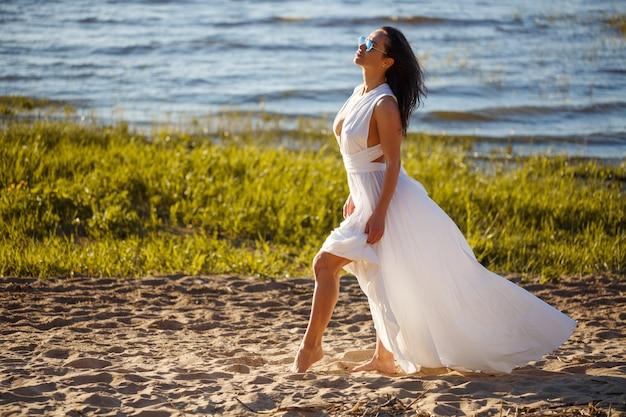 Schöne frau im weißen kleid, das am ufer der bucht an einem sonnigen sommertag aufwirft