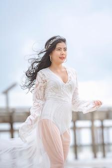Schöne frau im weißen kleid, das glücklich am strand spaziert, schöne frau gekleidet in der weißen brücke