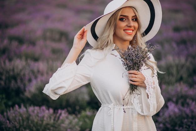 Schöne frau im weißen kleid in einem lavendelfeld