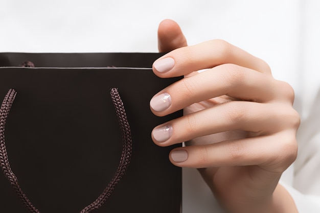 Schöne frau im weißen kleid mit perfektem beigem nagelentwurf, der braunes papierpaket hält.