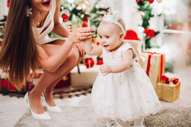 Schöne frau im weißen kleid mit reizendem kleinem baby