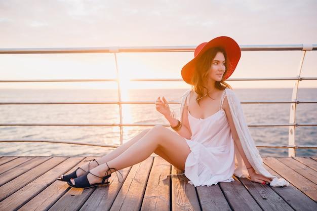 Schöne frau im weißen kleid sitzt am meer auf sonnenaufgang in der romantischen stimmung, die roten hut trägt