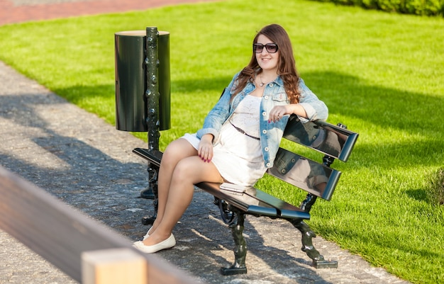 Schöne frau im weißen kleid sitzt auf einer bank im park mit tablet