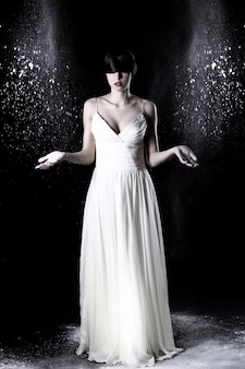 Schöne frau im weißen kleid und im fliegenden staub